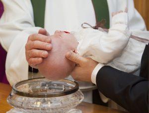 Pfarrer tauft Baby